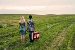 15213294-the-guy-with-girl-stand-in-the-field-in-which-hands-a-suitcase-with-a-text-love--Stock-Photo
